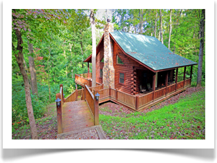 side view of cabin with tall green leave trees and stairs to wrap around porch